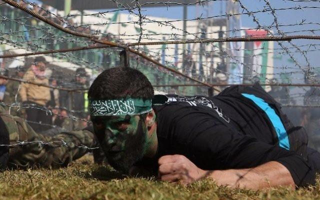 Un jeune Palestinien rampe sous un obstacle de barbelés lors d'une cérémonie de remise de diplôme pour un camp d'entraînement dirigé par le Hamas le 29 janvier 2015, à Khan Younis, dans le sud de la bande de Gaza. (Crédit : AFP / SAID KHATIB)