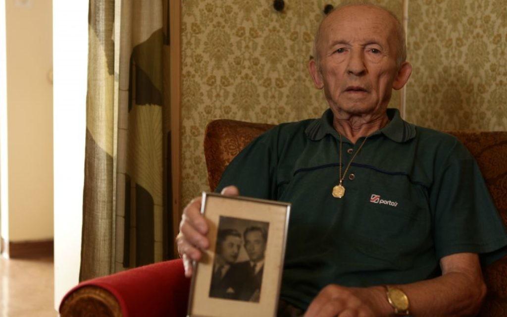 Stefan Weiss, avec une photo de sa famille, dans sa chambre à Reuth. (Crédit : Eldad Rafaeli)