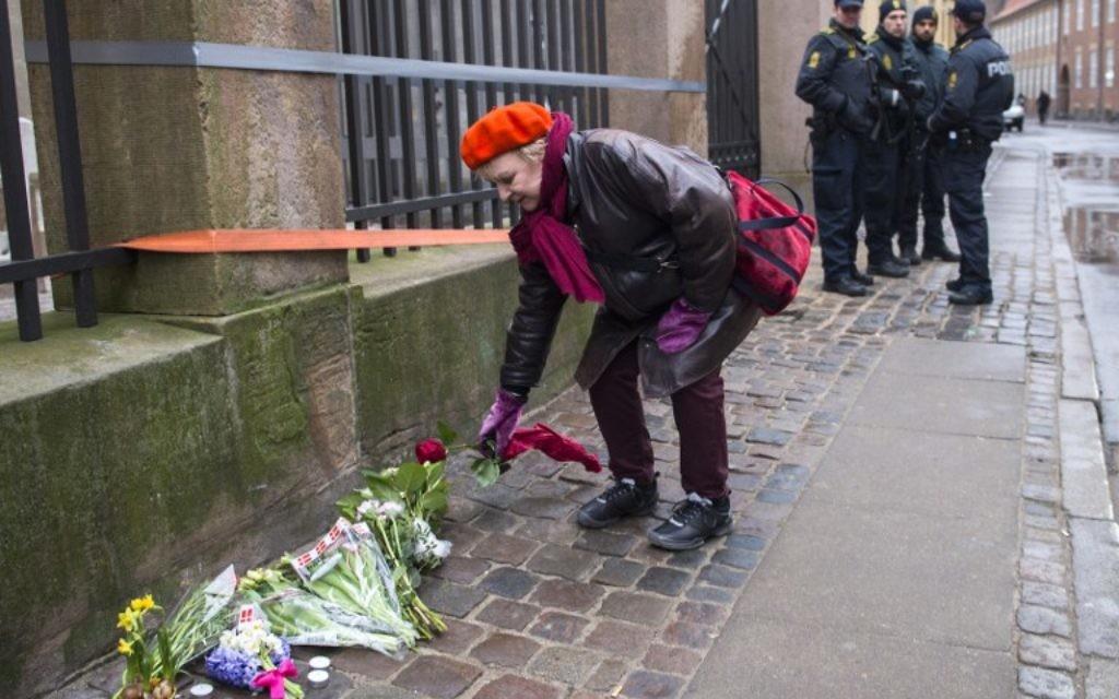Une femme qui dépose un bouquet de fleurs devant la synagogue de Copenhague - 15 février 2015 (Crédit : AFP)