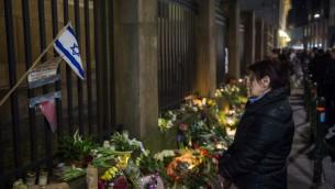 Des personnes venues honorer les victimes de la fusillade de Copenhague à l'extérieur de la synagogue principale de Copenhague le 15 février 2015 (Crédit : AFP/Odd Andersen)