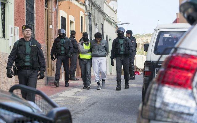 L'arrestation d'un des quatre hommes suspectés de recruter pour l'Etat islamique le 24 février 2015 (Crédit : AFP PHOTO / ANGELA RIOS)