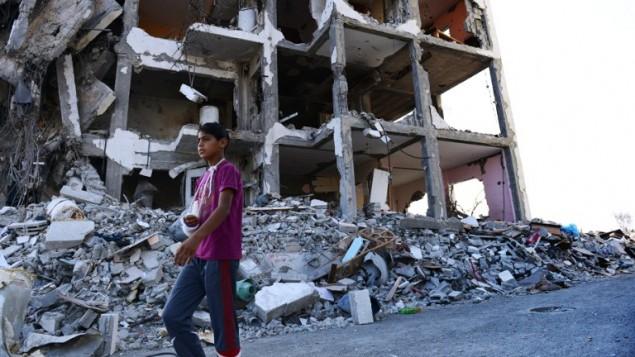 Feras Abu Inil, 13 ans, marchant près de son appartement détruit lors de l'affrontement entre les Israéliens et le Hamas cet été. La photo a été prise le 13 août 2013 (Crédit : AFP/Roberto Schmidt)