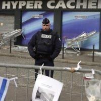 Un policier montant la garde le 21 janvier 2015 devant le magasin Hyper Cacher à Paris où quatre Juifs ont été  assassinés par Amédy Coulibaly, le 9 janvier 2015. (Crédit : Eric Feferberg/AFP)
