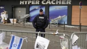 Un policier montant la garde le 21 janvier 2015 devant l'épicerie HyperCacher où quatre Juifs ont été tués par Amédy Coulibaly le 9 janvier 2015, à Pari (Crédit photo: Eric Feferberg / AFP)