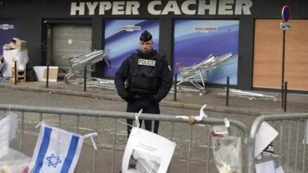 Un policier montant la garde le 21 janvier 2015 devant le magasin HyperCacher à Paris où quatre Juifs ont été  assassinés par Amédy Coulibaly le 9 janvier 2015 (Crédit photo: AFP/Eric Feferberg )