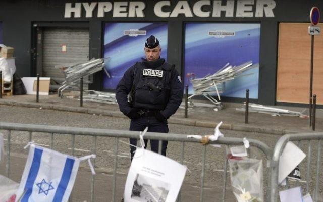 Un policier montant la garde le 21 janvier 2015 devant le magasin HyperCacher à Paris où quatre Juifs ont été  assassinés par Amédy Coulibaly, le 9 janvier 2015. (Crédit : Eric Feferberg/AFP)