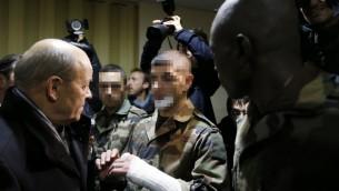 Le ministre français de la Défense, Jean-Yves Le Drian, s'entretenant avec les trois soldats attaqués par Moussa Coulibaly lors d'une patrouille à l'extérieur du centre communautaire juif de Nice le 3 février 2015 (Crédit : AFP/Valery Hache)