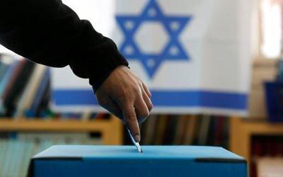 Un israélien met son bulletin dans l'urne (Crédit : Flash90)