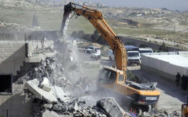 Un bulldozer de la municipalité de Jérusalem en train de détruire un immeuble illégalement construit dans le quartier d'A-tur à Jérusalem-est le 26 mars 2014 (Crédit : Sliman Khader/Flash90)