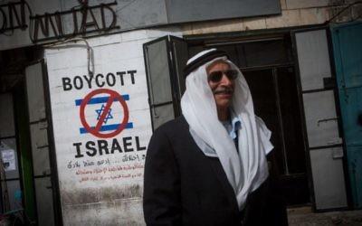 Un Palestinien passe à côté d'une affiche prônant le boycott d'Israël dans la ville de Bethléem en Cisjordanie le 11 février 2015 (Crédit : Miriam Alster/Flash90)