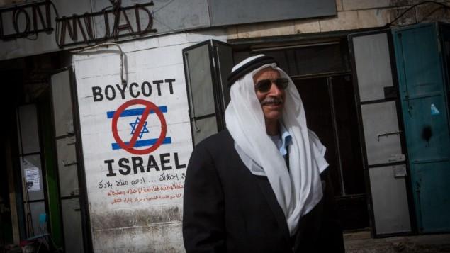 Un Palestinien passant à côté d'une affiche prônant le boycott d'Israël dans la ville cisjordanienne de Bethléem le 11 février 2015 (Crédit : Miriam Alster/Flash90)