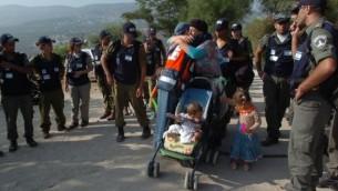 Deux femmes s'étreignent avant de laisser ses enfants à Sa Nur en Samarie, la police des frontières attendant de l'évacuer, le 23 août 2005 (Crédit : Nati Shohat / Flash90)