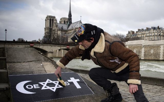 Un homme collant une affiche 'Coexist' de COMBO le 8 février 2015 sur le quai de la Tournelle, près de l'Institut du monde arabe (Crédit : Joel Saget/AFP)