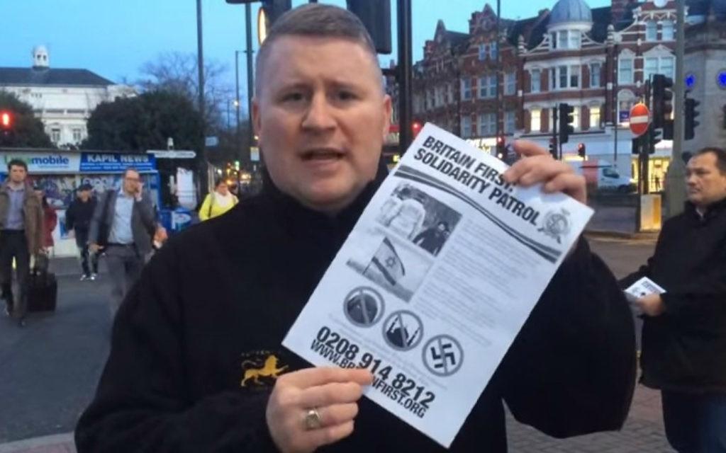 """Le dirigeant de Britain First tenant une affiche pour la """"patrouille de solidarité"""" dans un quartier juif de Londres en janvier 2015 (Crédit : Capture d'écran YouTube)"""