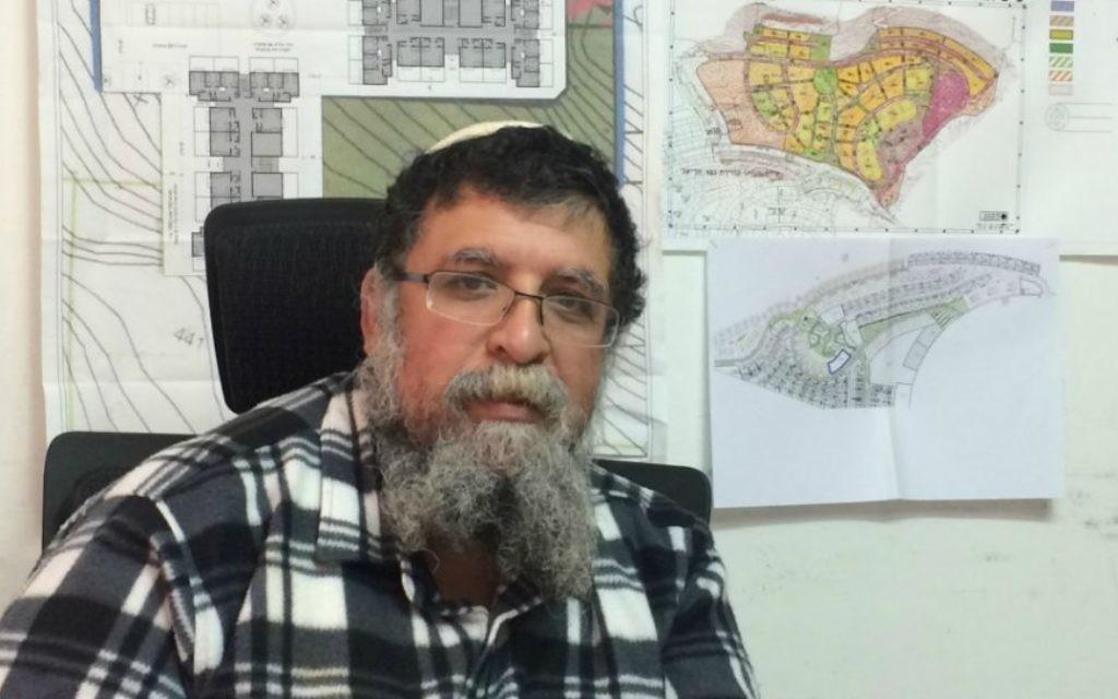 Arik Yefet, directeur de Netzer-Ariel, devant une carte de la zone où de nouvelles maisons destinées au familles de sa communauté sont en construction. (photo credit: Renee Ghert-Zand/Times of Israel)