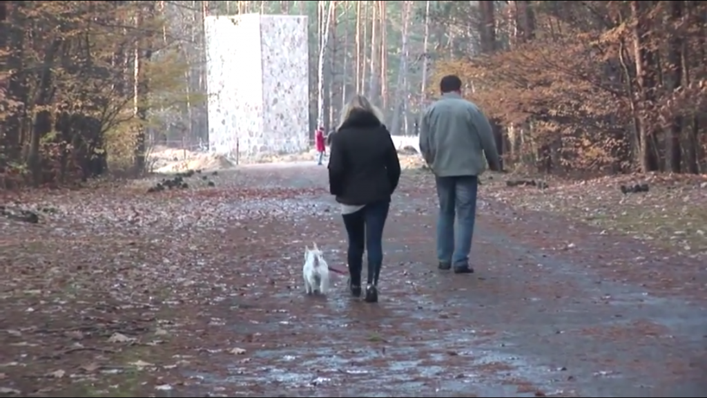 Un visiteur promenant son chien à l'endroit où se trouvaient les chambres à gaz à Sobibor en Pologne le 11 novembre 2014 (Crédit : Lena Klaudel)