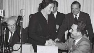 Les dirigeants du Mapai : Golda Meir serre la main du premier ministre israélien des Affaires étrangères, Moshe Sharett, après la signature de la Déclaration d'Indépendance. David Ben Gurion est à gauche (Crédit : Frank Shershel/ GPO)