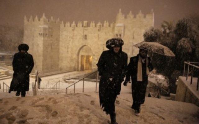 Des ultras-Orthodoxes marchant sous la neige près de la porte de Damas à Jérusalem le 19 février 2015 (Crédit : AFP PHOTO/AHMAD GHARABLI)