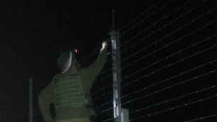Un soldat de Kometz , debout sur une échelle du côté gazaoui de la barrière de sécurité, pour réparer la clôture. Illustration. (Crédit : Netta Asner/unité des porte-paroles de l'armée israélienne)