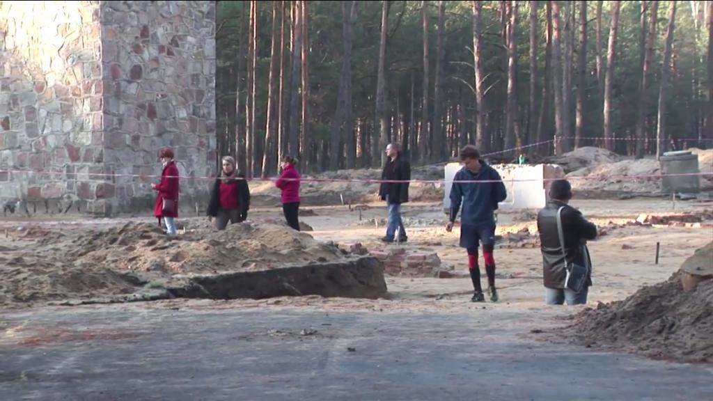 Des personnes se promenant à travers les restes des chambres à gaz récemment excavées le 11 novembre 2014 (Crédit :  Lena Klaudel)