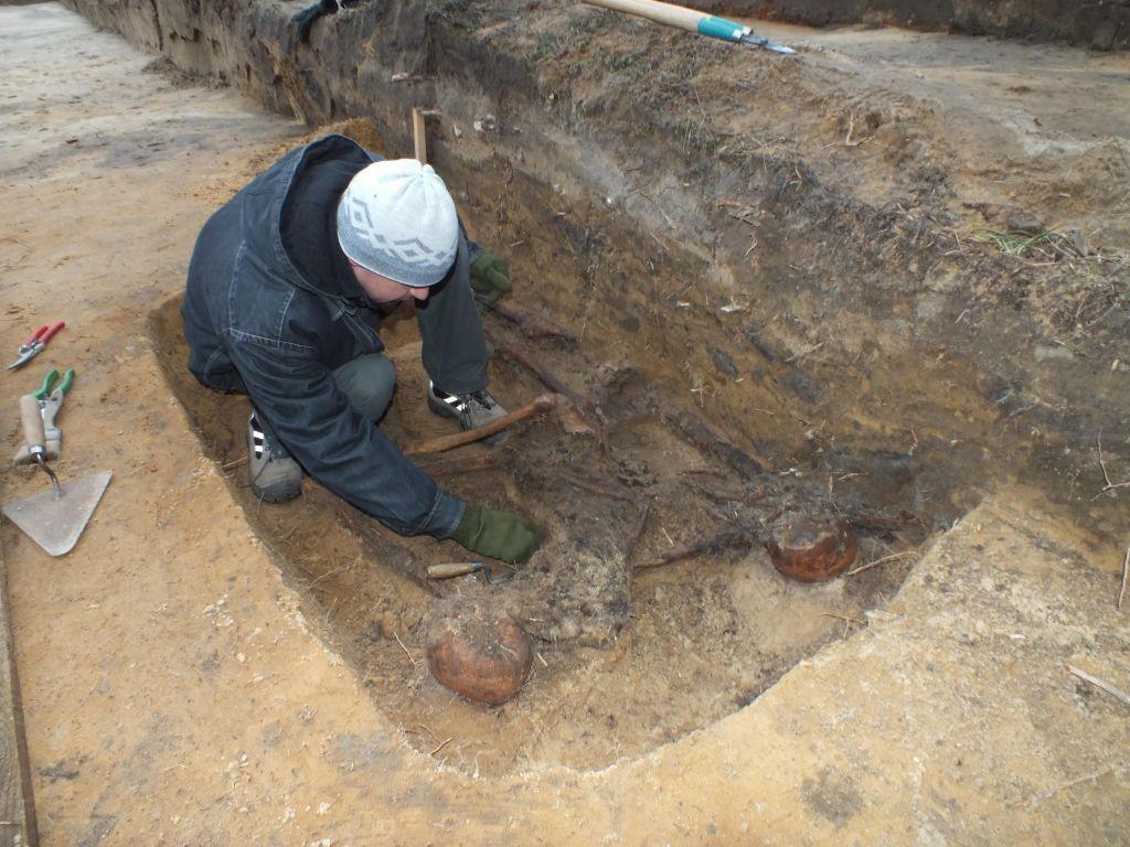 Un archéologue retrouvant un squelette à Sobibor en 2013 (Crédit : Wojtek Mazurek)