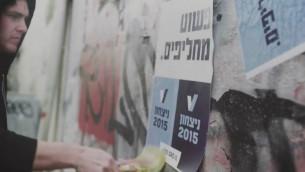 Des militants V15 collant des posters appelant aux changements (Crédit : YouTube/Victory2015)