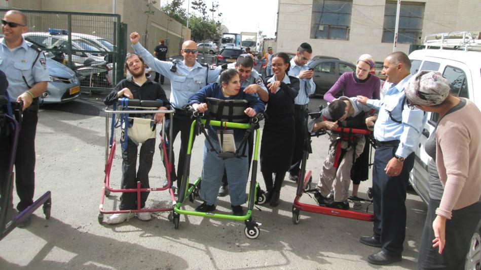 Les officiers de police de la station Leb Habira de Jérusalem aident les jeunes résidents d'ALEH à 'courir' pour le marathon de Jérusalem avec leur déambulateur (Crédit : Autorisation ALEH Jérusalem)