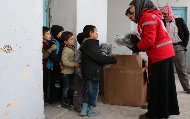 Des membres du Croissant rouge syrien distribuant des vivres à des enfants le 21 février 2015 à Alep (Crédit : AFP PHOTO / BARAA AL-HALABI)