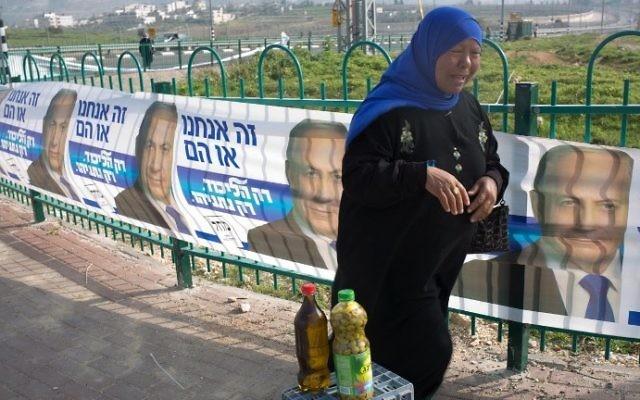 Une vendeuse palestinienne vendant de l'huile d'olive devant des affiches de campagne de Netanyahu le 10 mars 2015 à Givat Zeev, une implantation dans le nord de Jérusalem (Crédit : AFP/MENAHEM KAHANA)