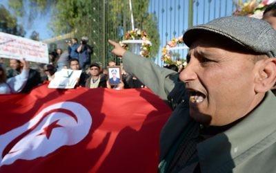 Des Tunisiens brandissant le drapeau pour protester contre l'attentat au musée Bardo - 19 mars 2015 (Crédit : AFP)
