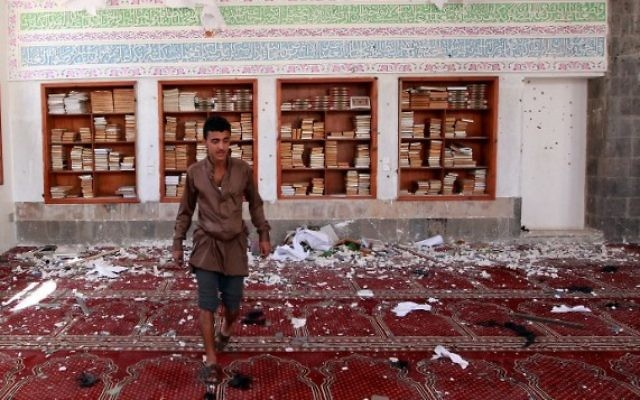 Un homme yéménite inspecte les dégâts suite à une explosion d'une bombe à la mosquée Badr dans le sud de Sanaa, le 20 mars, 2015. (Crédit : AFP / MOHAMMED HUWAIS)