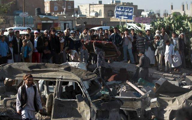 La population yéménite et les forces de sécurité se tiennent sur le site d'une frappe aérienne menée contre les Houthis près de l'aéroport de Sanaa le 26 mars, 2015, qui a tué au moins 13 personnes (Crédit : AFP PHOTO / MOHAMMED HUWAIS)