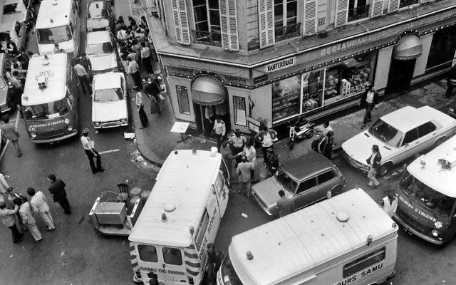 Les secours et la police rue des Rosiers, à Paris, après un attentat qui a fait six morts et 22 blessés, le 9 août 1982. (Crédit : Jacques Demarthon/AFP)