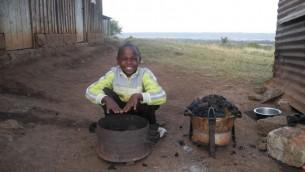 Le fils de Moshe Njogu réchauffe ses mains sur le feu. La haute altitude et le vent font de la région l'une des régions les plus froides du pays. (Crédit : Melanie Lidman / Times of Israël)