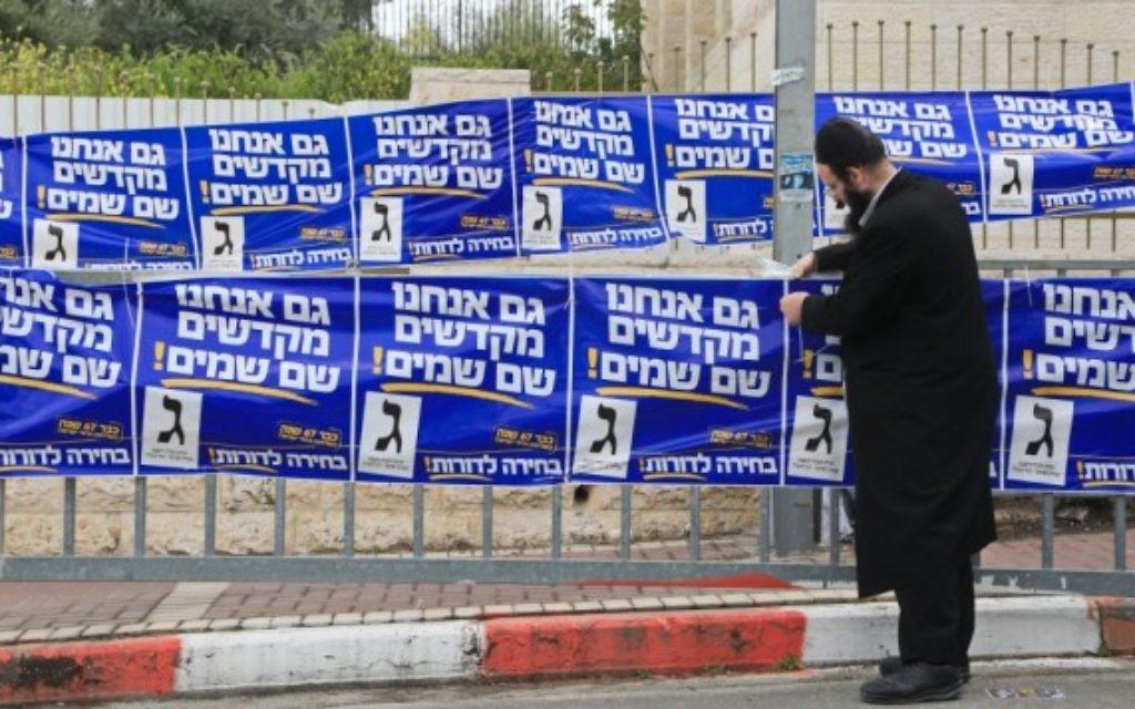 Un partisan ultra-orthodoxe de YaHadout HaTorah vu en train d'accrocher des affiches de campagne dans la ville de Beit Shemesh,  le 17 mars, 2015. (Crédit : Yaakov Naumi / FLASH90)