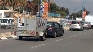 Un petit camion avec des affiches du Premier ministre Benjamin Netanyahu placardé dessus conduisant dans les rues de la ville du sud de Sderot (Crédit : Ilan Ben Zion/Times of Israel)