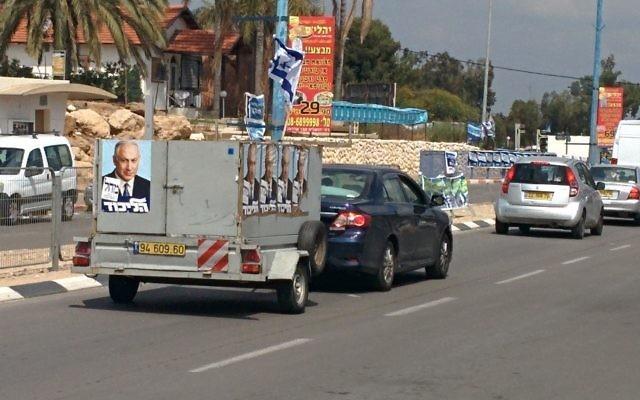 Un petit camion placardés d'affiches du Premier ministre Benjamin Netanyahu circule à Sderot (Crédit : Ilan Ben Zion/Times of Israel).