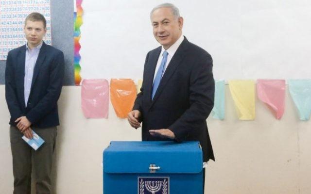 Le Premier ministre Benjamin Netanyahu et un de ses fils, à un bureau de vote de Jérusalem, le 17 mars 2015 (Crédit photo: Marc Israël Sellem / POOL / FLASH90)