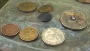 Des pièces de monnaie allemandes, datant de l'époque nazie, découvertes sur un site en Argentine qui auraient été construit comme un repaire pour des criminels de guerre nazis. (Crédit : Capture d'écran YouTube / AllNews)