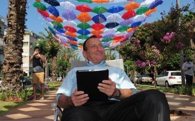 Le maire de Tel-Aviv, Ron Huldai, surfe sur Internet sous le toit de 600 parasols colorés qui décorent le boulevard Rothschild pour lancer le nouveau « cloud Wi-Fi » dans sa ville (Crédit : Kfir Sivan)