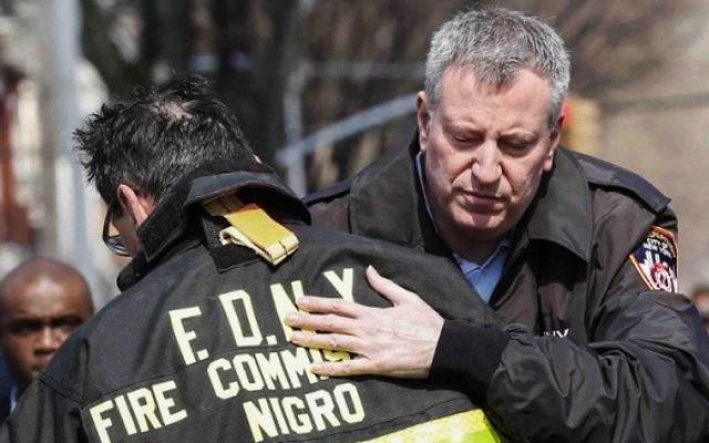 Le Maire de New York Bill de Blasio enlace le commandant des pompiers de New York Daniel Nigro  devant la maison en feu dans le quartier Midwood à Brooklyn le 21 mars 2015  (Crédit photo: Kena Betancur / Getty Images / AFP)