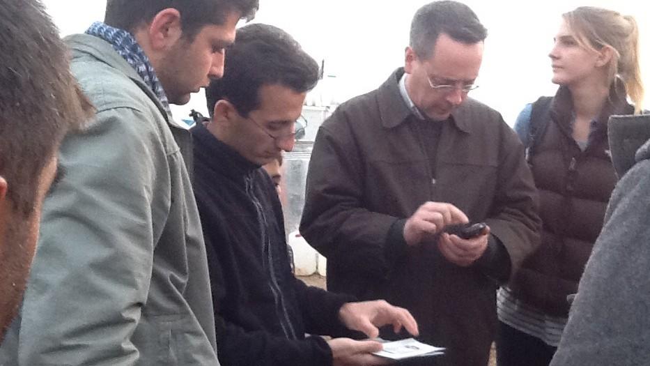 Fuad Jamal (à gauche), Hiwa Sherzad, et Jonathan Miles inspectent les papiers d'identité d'un famille de réfugiés kurde dont le bébé a besoin d'une intervention chirurgicale en Israël (Crédit : Times of Israel/Lazar Berman)