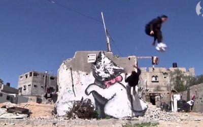 Des traceurs de parkour de Gaza sautant devant un graffiti de l'artiste britannique Banksy dans leur ville. (Capture d'écran: Youtube/The Guardian)