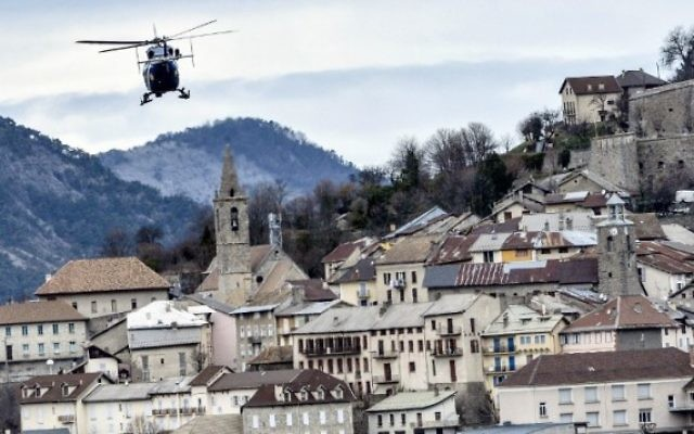 Un hélicoptère de la gendarmerie française survole Seyne-les-Alpes le 28 mars, 2015, près du site où un vol de Germanwings s'est écrasé dans les Alpes françaises, tuant la totalité des 150 passagers. (Crédit photo: AFP / JEFF PACHOUD)