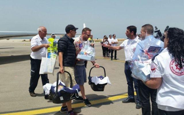 Le ministre de l'intérieur Gilad Erdan (2nd à droite) et le directeur de Magen David Adom, Eli Bean (3ème à droite) accueillent les parents qui arrivent avec leurs nouveau-nés en Israël, le 27 avril 2015. (Crédit : MDA)