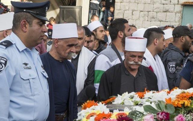 Les amis, les parents et les dignitaires religieux pleurent devant le cercueil de l'agent de  police israélien Zidan Saif, 30 ans, membre de la communauté druze d'Israël, lors de ses obsèques dans son village de Yanouh-Jat, le 19 novembre 2014 (Crédit : AFP / Jack Guez)