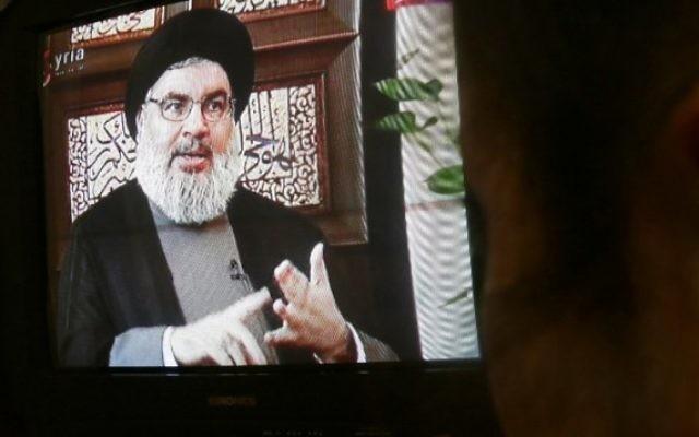 Un syrien regarde une interview de Hassan Nasrallah diffusé sur la chaîne de télévision officielle syrienne Al-Ikhbariya, à Damas, le 6 avril 2015. (Crédit : AFP / STR)