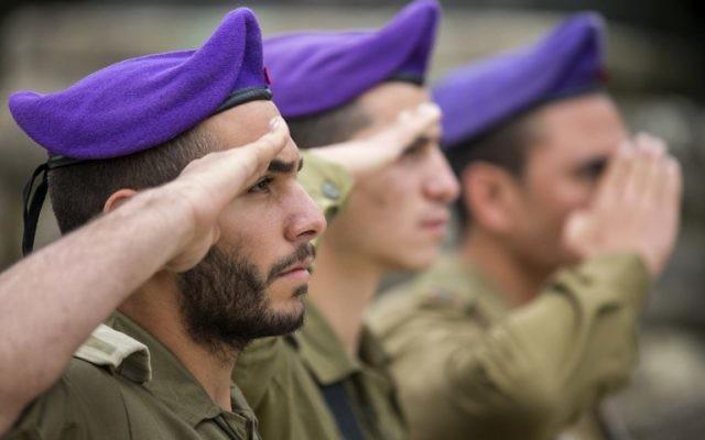 Des soldats israéliens observent les minutes de silence pour Yom HaShoah (Crédit : Jack Guez/AFP)