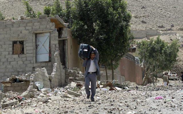 Un homme transporte ses affaires après que sa maison ait été bombardée - Yémen - 22 avril 2015 (Crédit : AFP)
