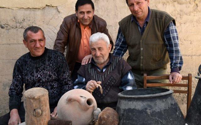 Une photo prise le 24 février, 2015 montre Mnatsakan Muradyan (C), le petit-fils de Martiros Muradyan, posant avec ses parents dans le village de Poker Vidéo, au sud d'Erevan, près de la montagne Ararat en Arménie. Les descendants de Martiros Muradyan chérissent comme des reliques religieuses les quelques objets qu'il a pu prendre avec lui quand il a fuit les massacres il y a cent ans (Crédit : AFP PHOTO / KAREN MINASYAN)